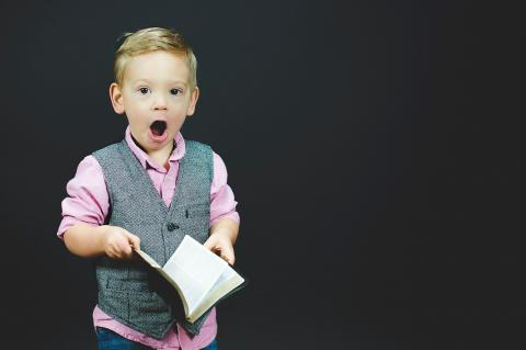 A kid holding a Bible looking shocked