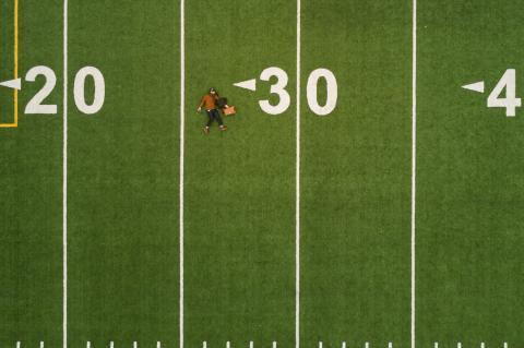 Football field with a guy fallen over